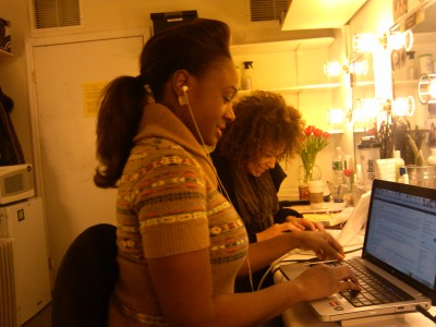 Andrea Dora and Saycon Sengbloh using backstage tech time to work online.
